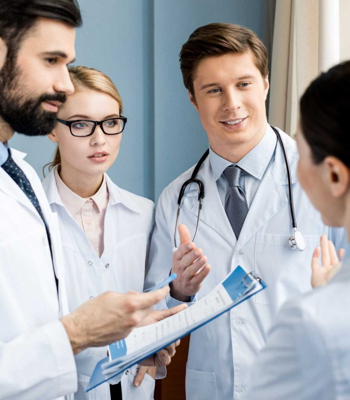 side-view-of-doctors-team-discussing-diagnosis-in--H9FJMNX